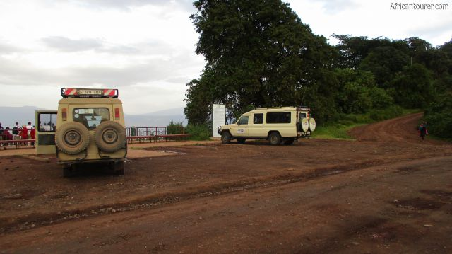 Ngorongoro crater view point 1, on the left with safari vehicles parked infront of it and road to Olmoti on the far right