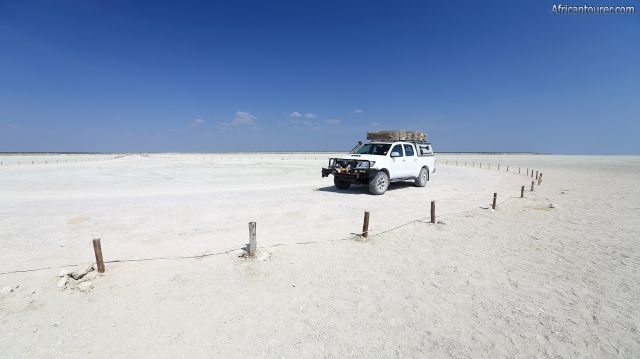 Etosha lookout point, an SUV parked on it with the Etosha pan in the background<sup>1</sup>