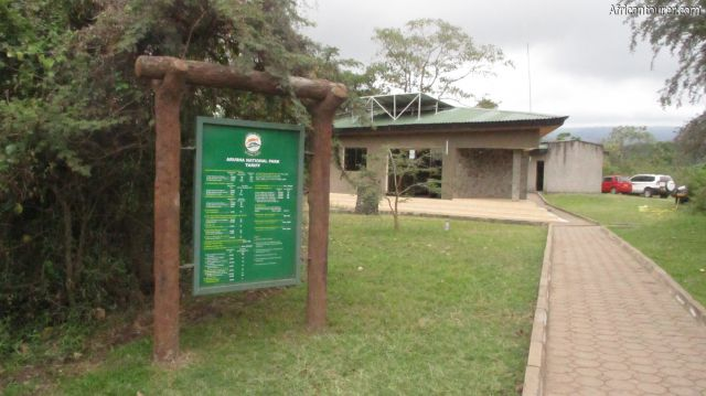 Ngongongare gate of Arusha national park, a signpost for park fees (near left) with TANAPA offices in the distance