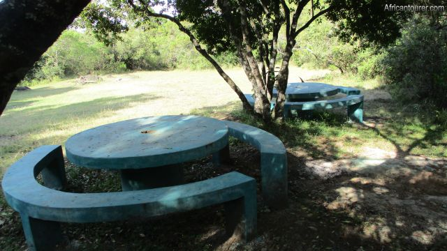 Public campsite number 3 of Arusha national park, concrete dining benches (near) with rest of campsite in the distance and camp buildings behind viewer (off view)