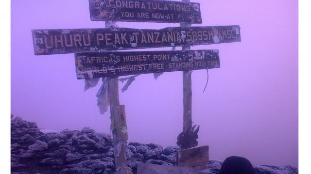 Uhuru peak of mount Kilimanjaro, old sign post with a snow covered ground at dawn